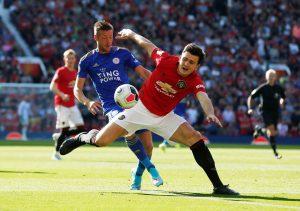 Manchester United's Harry Maguire in action with Leicester City's Jamie Vardy.
