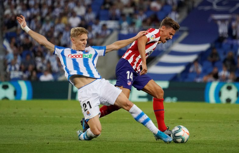 Real Sociedad's Martin Odegaard in action with Atletico Madrid's Marcos Llorente.
