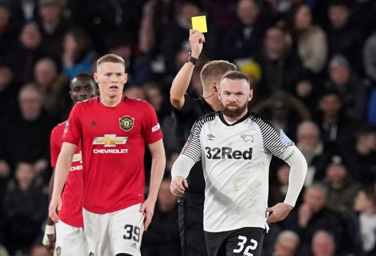 Wayne Rooney is shown a yellow card by referee.