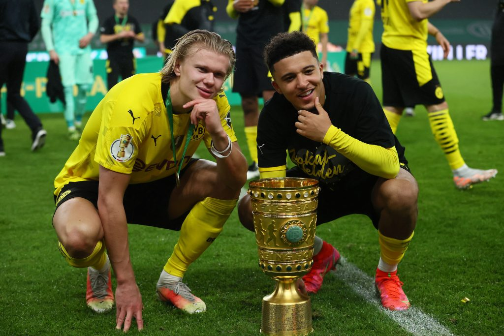 Erling Braut Haaland and Jadon Sancho celebrate winning the DFB Cup trophy.