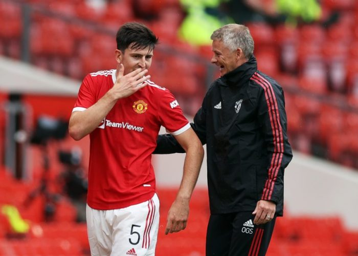 Manchester United's Harry Maguire speaks with manager Ole Gunnar Solskjaer as he walks off to be substituted.