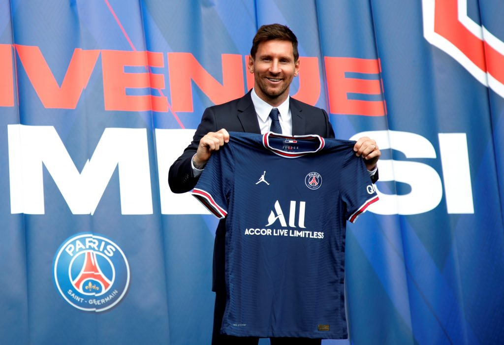 Paris Saint Germain's Lionel Messi poses with a shirt on the pitch after the press conference.