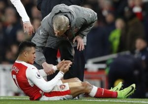 Arsenal manager Arsene Wenger speaks with Alexis Sanchez as he sits injured.